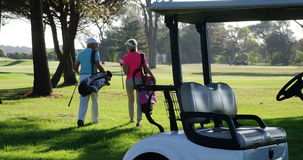Two golfers walking together with golf bag. At golf course stock video footage