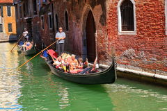 Two gondolas with passengers near the old building Royalty Free Stock Images