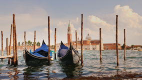 Two gondolas at the pier against the backdrop of the coastline of Venice, Italy. In the foreground, water splashes, slow stock video footage