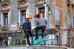 Two gondoliers on the bridge in Venice. Stock Images