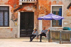 Two gondoliers on the docks awaiting tourists in Venice, Italy Stock Photos