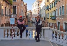 Two gondolier men on a bridge in Venice royalty free stock images