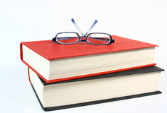 Two Good Books with Glasses. Two old books stacked with a pair of eye glasses sitting on top. Photographed on a white background Stock Images
