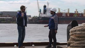 Two good friends, dockers and colleages give high five and say goodbye in Shipping cargo port.  stock video footage