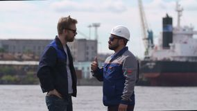 Two good friends, dockers, coworkers and colleages give high five in Shipping cargo port. Two dockers, coworkers and colleages shake hands in Shipping cargo port stock video
