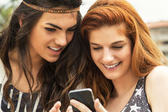 Two good friends reading message on the mobile phone Stock Images