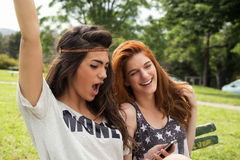 Two good friends reading message on the mobile phone Royalty Free Stock Images