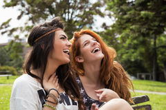 Two good friends reading message on the mobile phone. In the park Royalty Free Stock Photography
