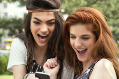 Two good friends reading message on the mobile phone Royalty Free Stock Image