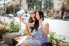 Two good looking thin girls with long dark hair,dressed in casual stye,sit at the bench and take a selfie, royalty free stock photo