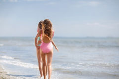 Two good-looking young girls in colorful swimsuits on a sea background. Ladies walking along a beach. Copy space. Stock Photo