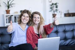Happy teenage girls sitting on a sofa with a laptop while showing thumb up stock photography
