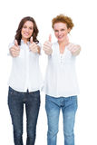 Two gorgeous casual models posing with thumbs up Stock Photos