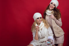 Two gorgeous girlfriends with perfect smiles wearing white woolen hats, scarves, sweaters and waistcoats in the red background Stock Images