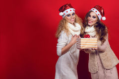 Two gorgeous girlfriends with shining smiles wearing Santa hats and warm woollen scarves giving present box Stock Image