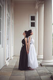Two gorgeous girls in black and white long dresses Royalty Free Stock Image