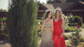 Two gorgeous girls in long gowns and crowns in a. Two gorgeous girls in long gowns and crowns in the garden with roses stock footage