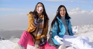 Two gorgeous laughing young woman in snow stock footage