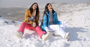 Two gorgeous laughing young woman in snow Royalty Free Stock Photos