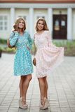 Pretty girls in rose and blue flowery dresses posing and smiling. Two gorgeous and pretty ladies with slender figures wearing flowery blue and rose cute dresses royalty free stock images