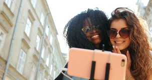 Two gorgeous smiling girls are correcting hair and hugging while taking selfies on the mobile phone. One of them is afro stock footage