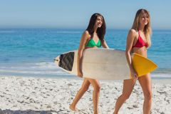 Two gorgeous women in bikinis holding a surfboard Royalty Free Stock Photo
