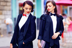 Two gorgeous women posing in black suits Royalty Free Stock Image