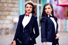 Two gorgeous women posing in black suits Royalty Free Stock Images