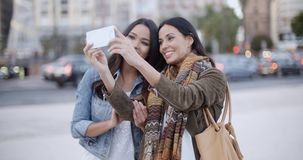 Two gorgeous women posing for a selfie. Two gorgeous women posing together for a selfie on a mobile phone as they stand outdoors in an urban square or park stock footage