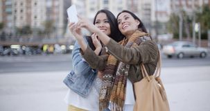 Two gorgeous women posing for a selfie. Two gorgeous women posing together for a selfie on a mobile phone as they stand outdoors in an urban square or park stock video