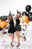 Two gorgeous women wearing black dresses, witch hats and high heels hold black and orange balloons. Halloween party stock photography