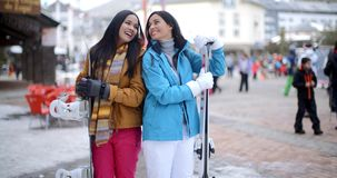 Two gorgeous young brunette snowboarders. Standing close together in a mountain ski resort smiling and chatting as they holds their snowboards stock video footage