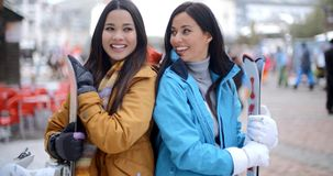 Two gorgeous young brunette snowboarders. Standing close together in a mountain ski resort smiling and chatting as they holds their snowboards stock footage