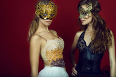 Two gorgeous young women in golden and bronze masks standing on dark red background. Blonde is staring straight, brunette looking down and smiling. Studio shot Stock Images