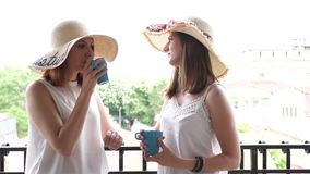 Two gorgeous young women in large summer hats on the balcony drinking coffee and talking. Slow motion footage stock footage