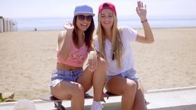 Two gorgeous young women laughing and joking. Two gorgeous young women in baseball caps sitting in the sunshine at the seaside laughing and joking stock video