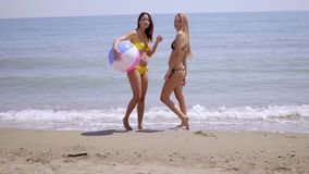 Two gorgeous young women posing with a beach ball stock video