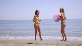 Two gorgeous young women posing with a beach ball stock video footage