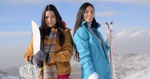 Two gorgeous young women posing with snowboards. On a snowy mountain summit against a cloudy sunny blue sky smiling happily at the camera stock footage