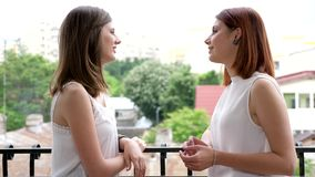 Two gorgeous young women talking to each other and laughing. On the balcony. Slow motion stock footage
