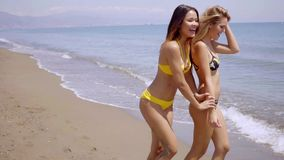 Two gorgeous young women wearing bikinis. Strolling along the edge of the sea on a tropical beach chatting and smiling happily stock video footage