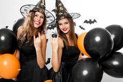 Two gorgious women in black dresses and witch hats hold black and orange balloons. Halloween stock photography