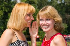 Two gossiping girls outside. Stock Photo