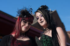 Two Goth Ladies in the Sunshine. Two ladies in provocative Victorian attire in the sunshine at the Whitby Goth festival in Whitby, North Yorkshire, England UK in stock photography