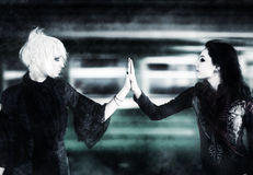 Two goth women touching hands. On moving train background stock images