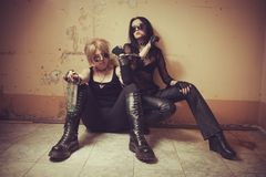 Two gothic babes. Two young seductive gothic girl sitting on the floor royalty free stock image
