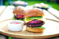 Two gourmet burgers with sauce on the side outdoors. Stock Photos
