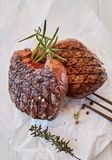 Two gourmet medallions of grilled fillet steak. Two gourmet medallions of thick juicy grilled fillet beef steak seasoned with peppercorns and fresh thyme and royalty free stock photo