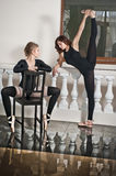 Two graceful ballerinas, one doing the splits and one sitting on chair, on the marble floor. Gorgeous ballet dancers Stock Photo