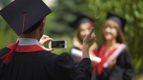 Two graduate girls holding diplomas and posing for smartphone camera, graduation. Stock footage stock footage
